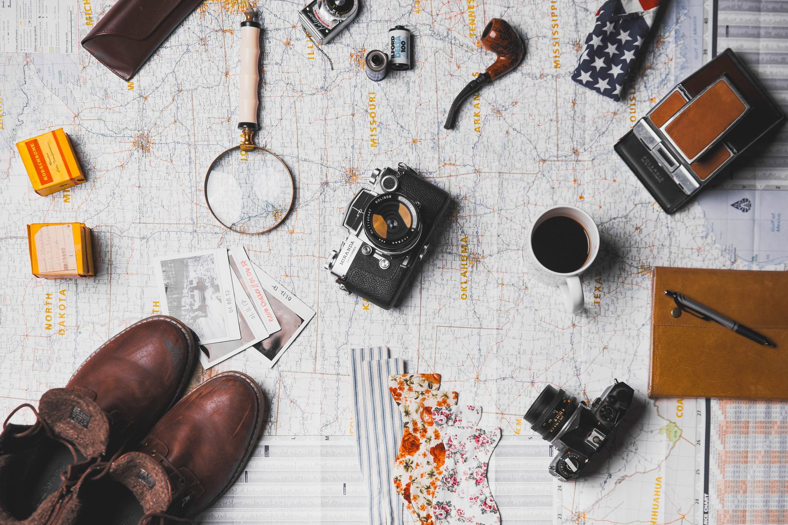 Aerial view of miscellaneous traveling equipment scattered across a map to indicate planning and organization beforehand are career skills you learn from traveling