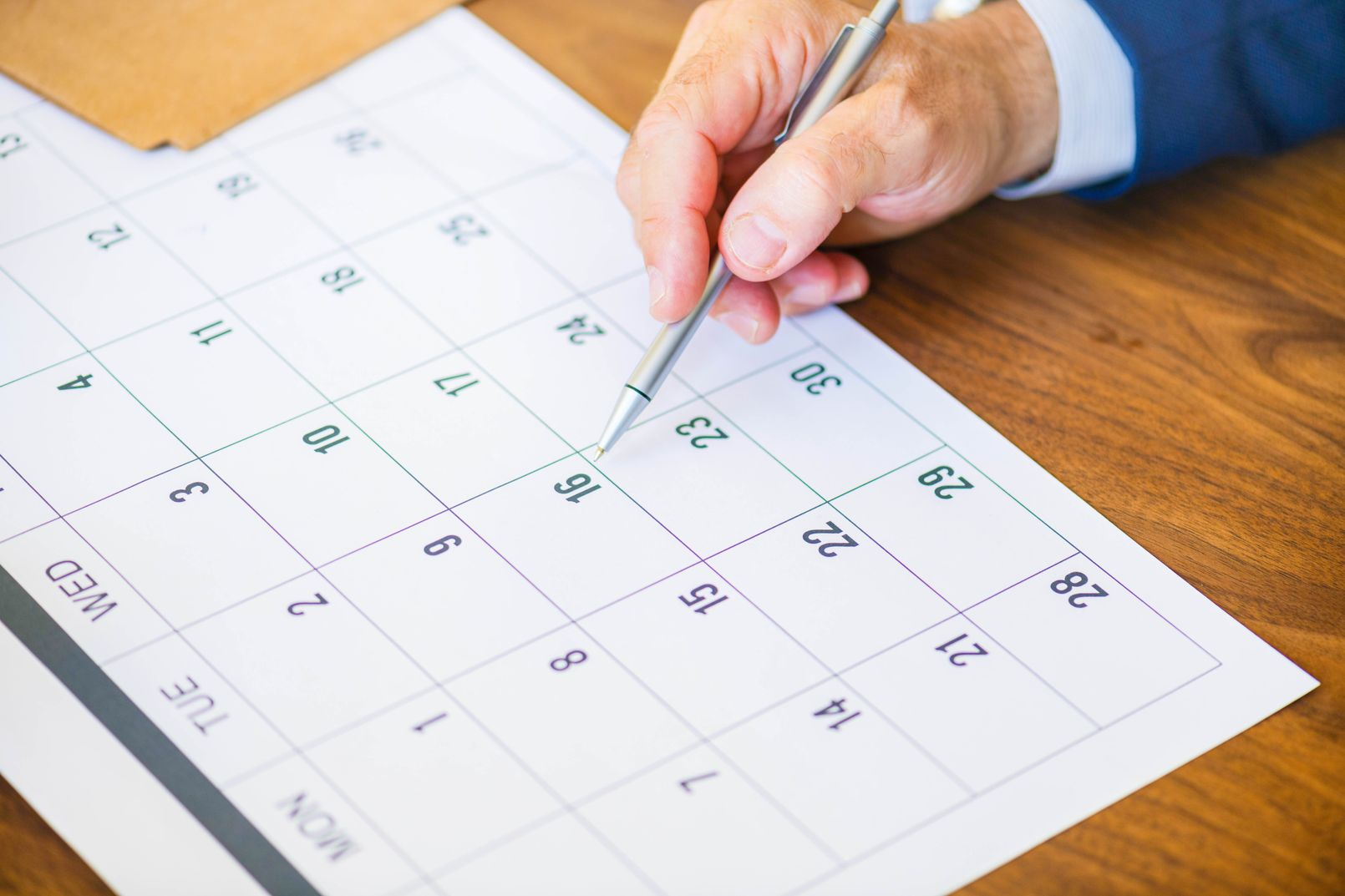 Man's hand holding a pen and pointing to a calendar, undoubtedly setting a deadline for a task to facilitate effective time management