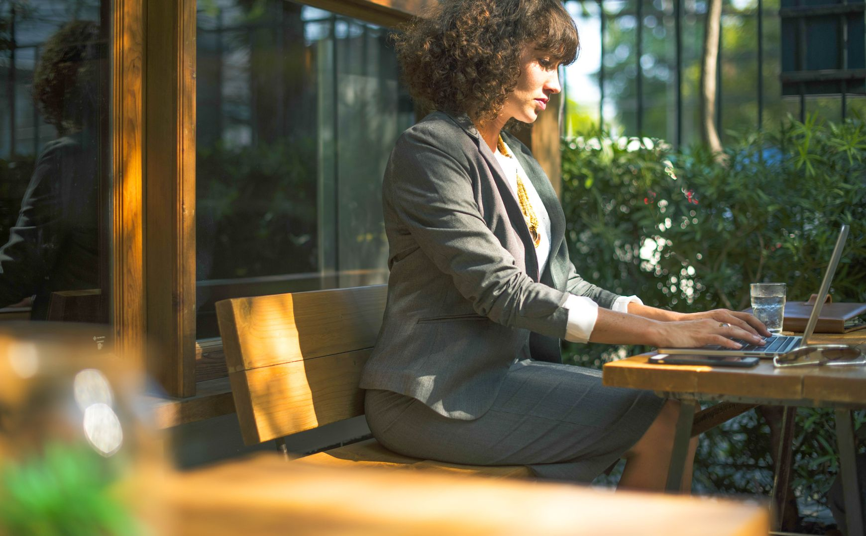 Woman in business attire sitting on bench while typing on her laptop