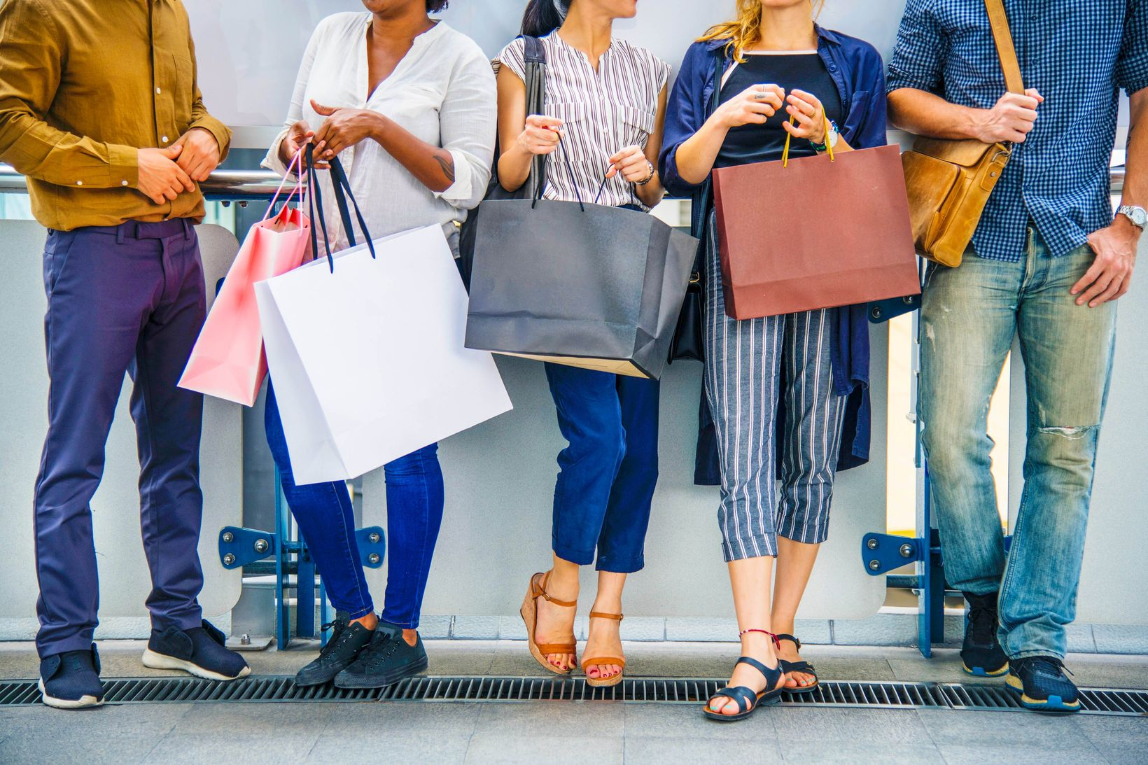 Group of friends standing in array holding numerous shopping bags, clearly indicating that the importance of budgeting is lost on them