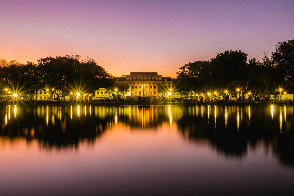 Buildings, trees, and night lights reflected on a body of water at sunset