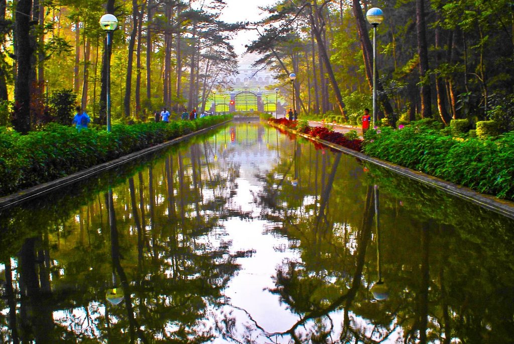 Pine trees, hedgerows, lampposts, and passersby reflected on a clear body of water in Wright Park in Baguio City, one of the best places to visit in the Philippines