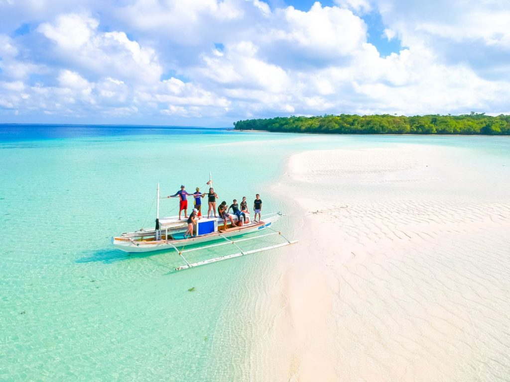 An outrigger boat laden with people docked on a white sandbar that leads to a forested island, all of which are surrounded by turquoise waters