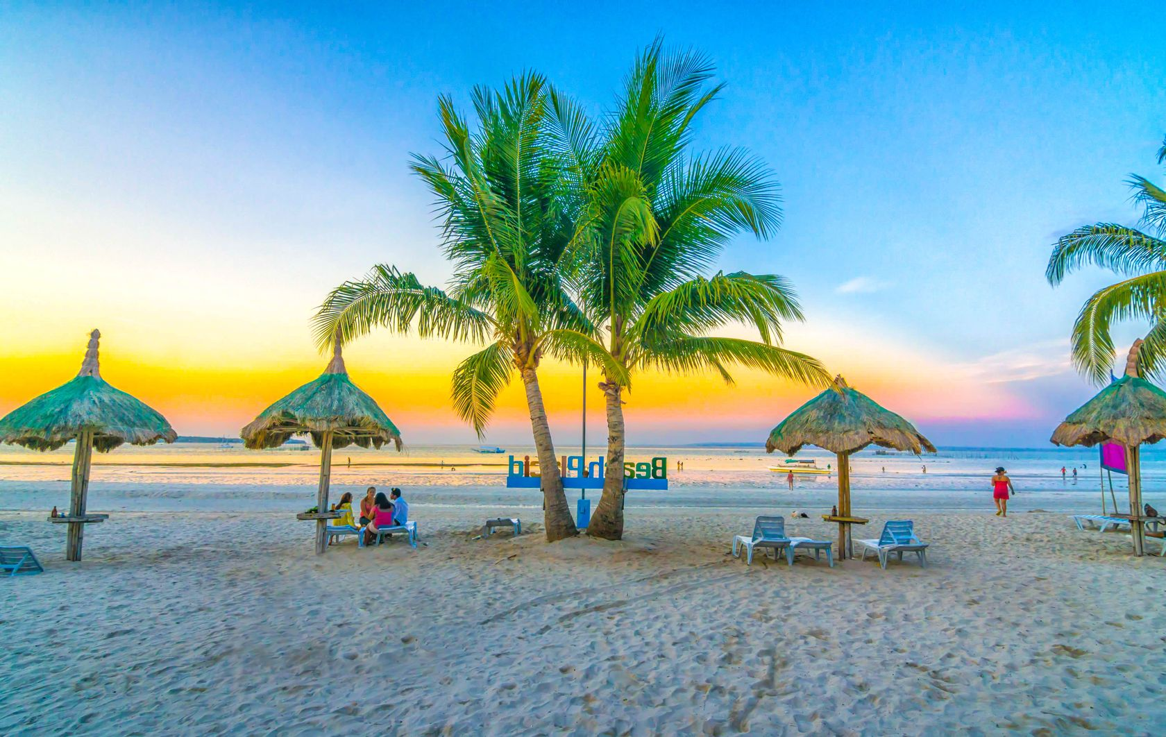 Tropical sandy beach with palm trees and huts with people lounging about in Bantayan Island, one of the best places to visit in the Philippines
