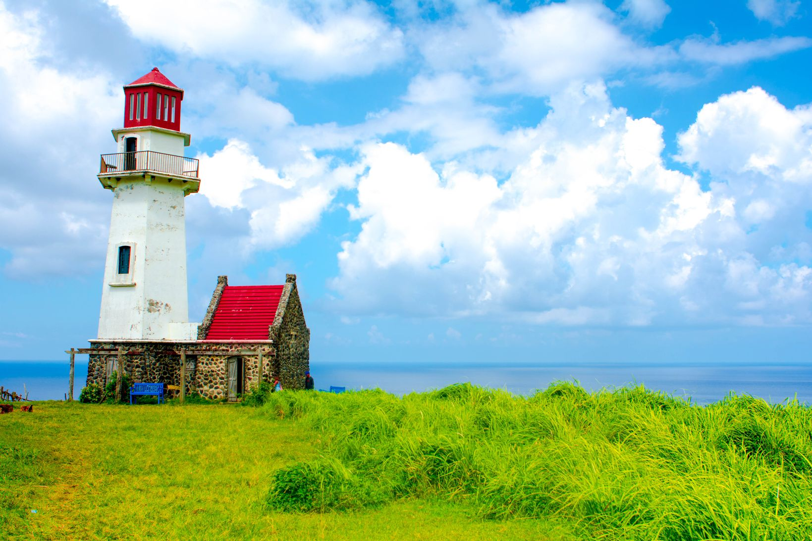 A white-bodied, red-topped lighthouse and a stone house with a similarly red roof stand on a grassy land overlooking the blue sea in Batanes, one of the most beautiful places to visit in the Philippines