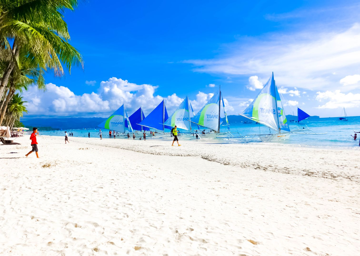 An array of outrigger sailboats moored on a white sandy beach with palm trees in Boracay Island, one of the best places to visit in the Philippines