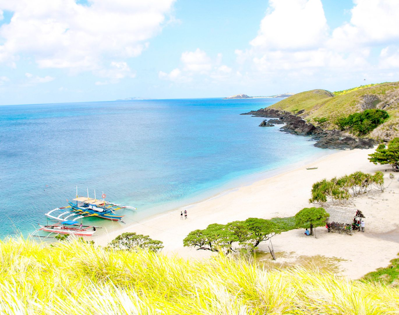 A white sandy beach at the feet of grassy hills, facing the blue sea