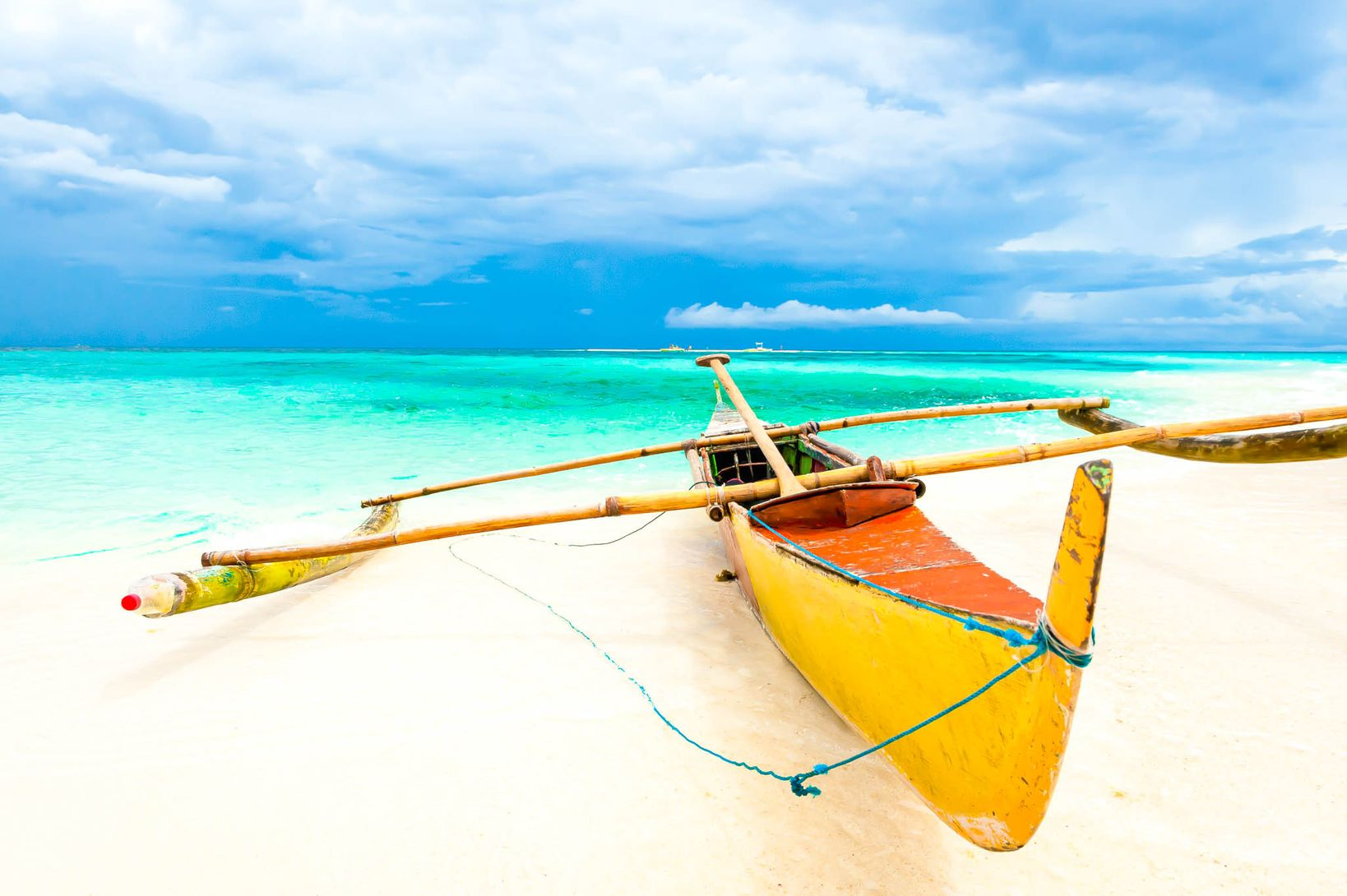 An orange and yellow-painted outrigger boat moored on a white sandy shore fronting turquoise and blue waters in Camiguin, one of the best places to visit in the Philippines