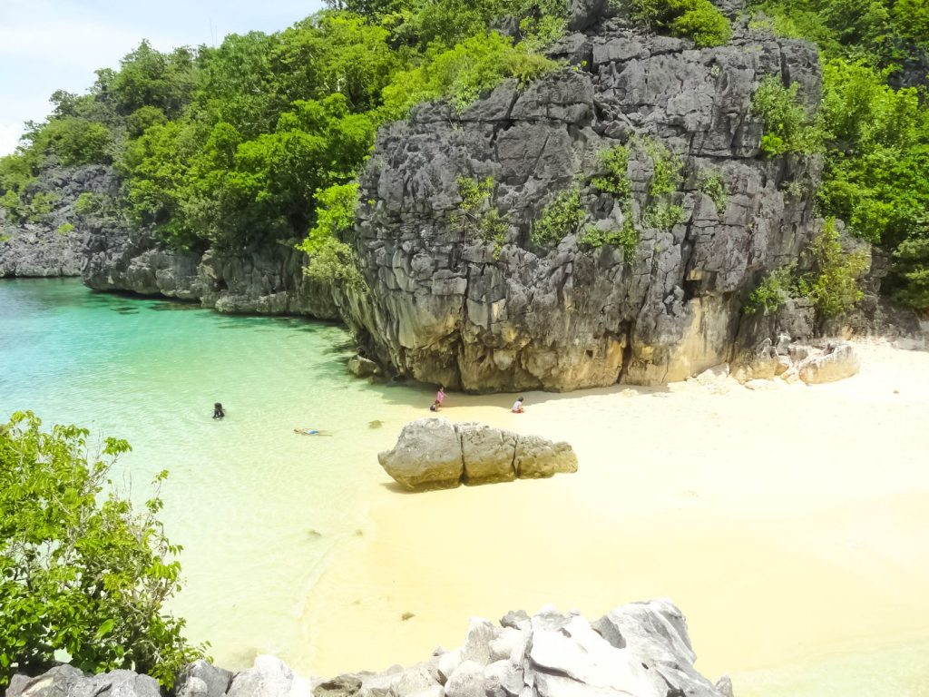 White sandy beach with rocky limestone cliffs overhung with vegetation fronting turquoise waters in Caramoan, one of the best places to visit in the Philippines