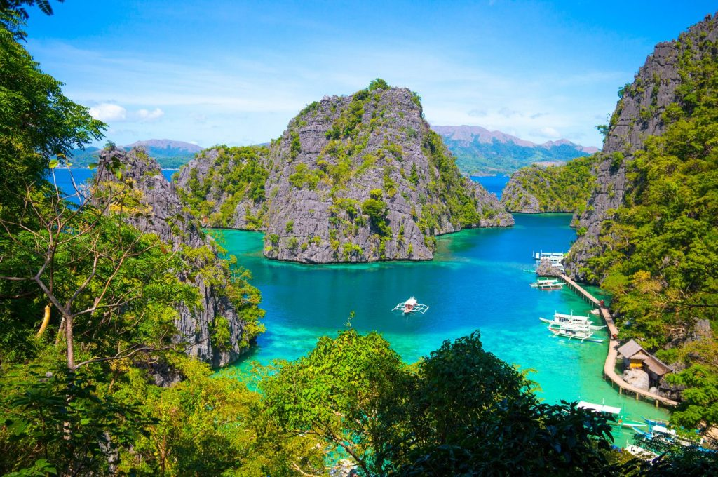 A bay with blue and turquoise waters surrounded by dark limestone cliffs and outcrops overhung with vegetation in Coron, one of the best places to visit in the Philippines