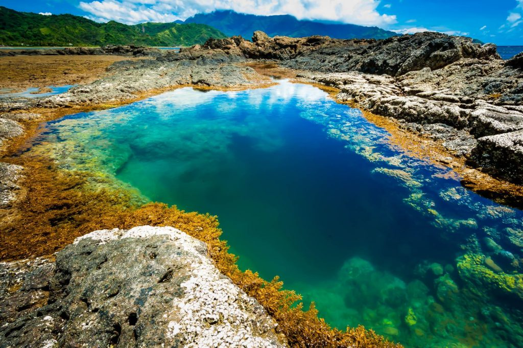 A crystal-clear pool of turquoise and blue-hued waters surrounded by rocks in Dingalan, one of the best places to visit in the Philippines