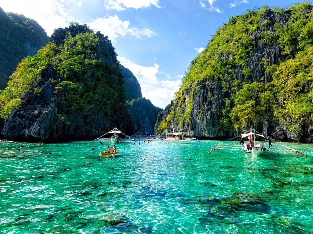 Laden outrigger boats and numerous people occupy the crystalline waters of a turquoise-hued lagoon surrounded by dark limestone cliffs in El Nido, one of the best places to visit in the Philippines