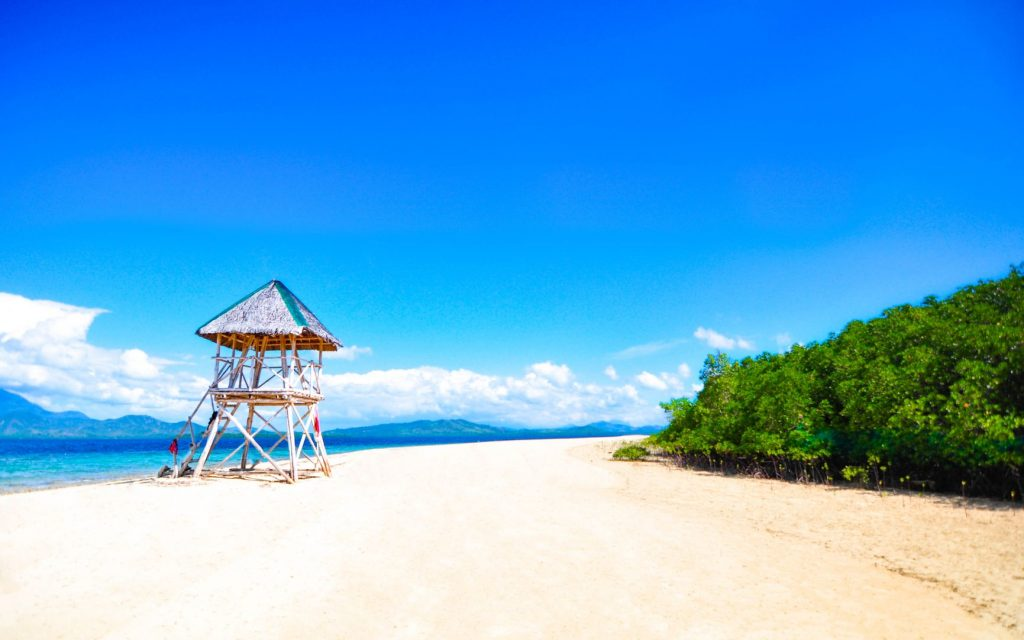 A lifeguard tower stands on a white sandy beach bounded on one side by dense vegetation
