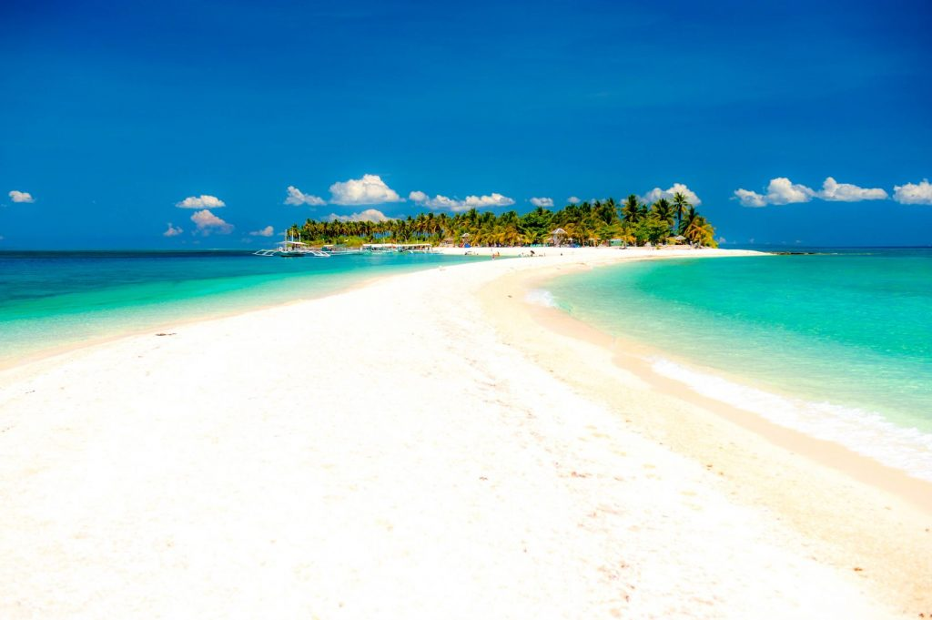 A white sandbar extends from the coast of a small palm-covered island fringed with a white sandy shore surrounded by turquoise waters