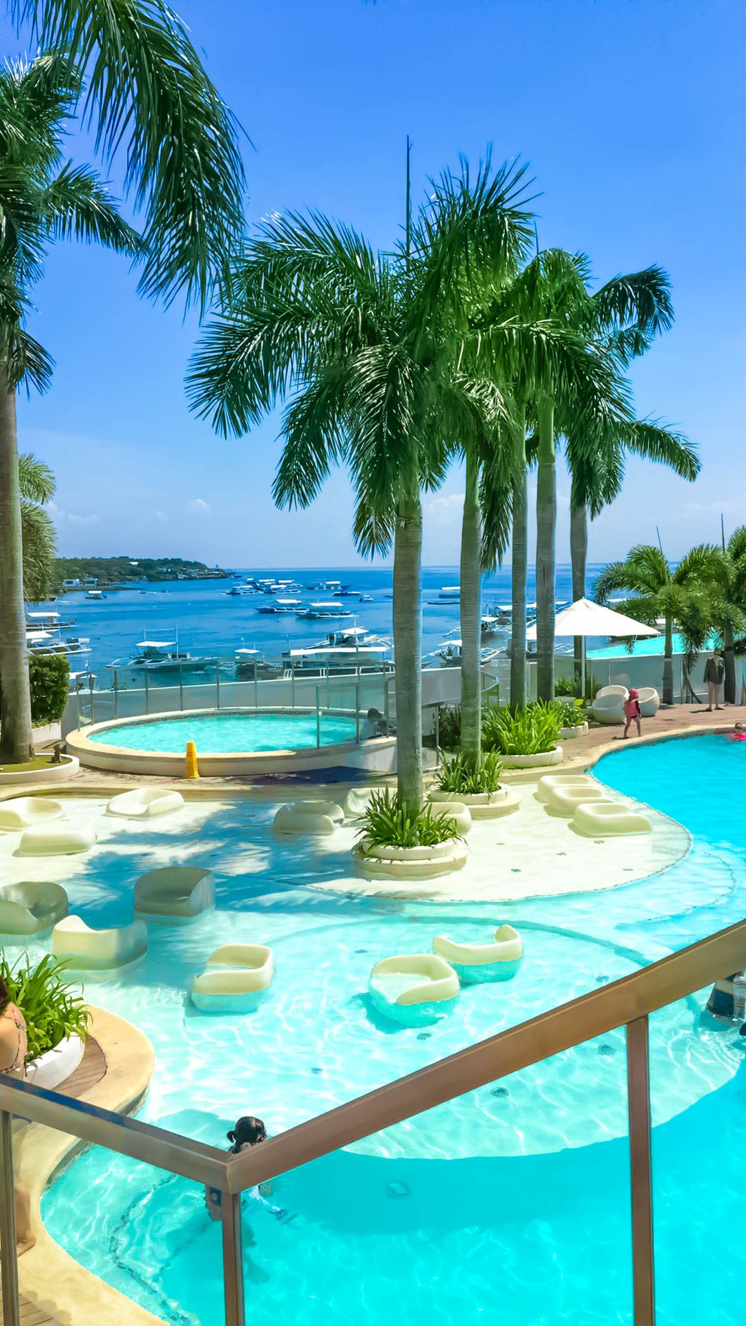 Resort with pools and coconut palms overlooking the sea in Mactan Island, one of the best places to visit in the Philippines