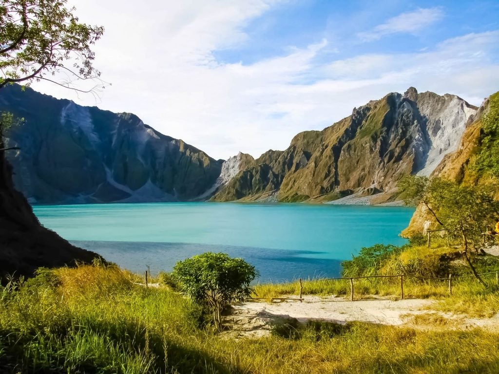 Turquoise-hued lake at the crater of a volcano, surrounded by the volcano's walls clad in vegetation