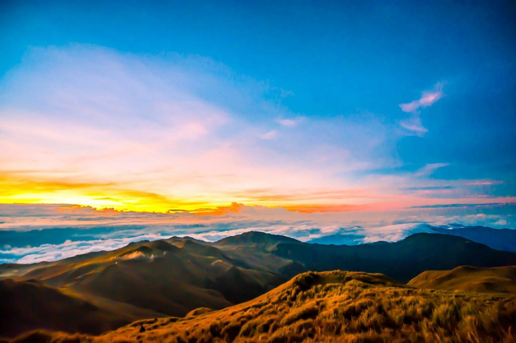 Grassland summit of a mountain overlooking a sea of clouds all illuminated by the rising sun in Mount Pulag, Benguet, one of the best places to visit in the Philippines