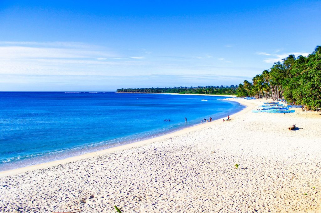 White sandy beach with coconut palm groves fronting the blue sea in Pagudpud, one of the best places to visit in the Philippines