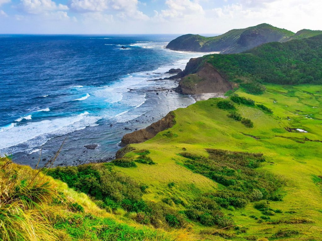 Verdant rolling hills ending on towering cliffs overlooking the blue sea in Palaui Island, one of the best places to visit in the Philippines