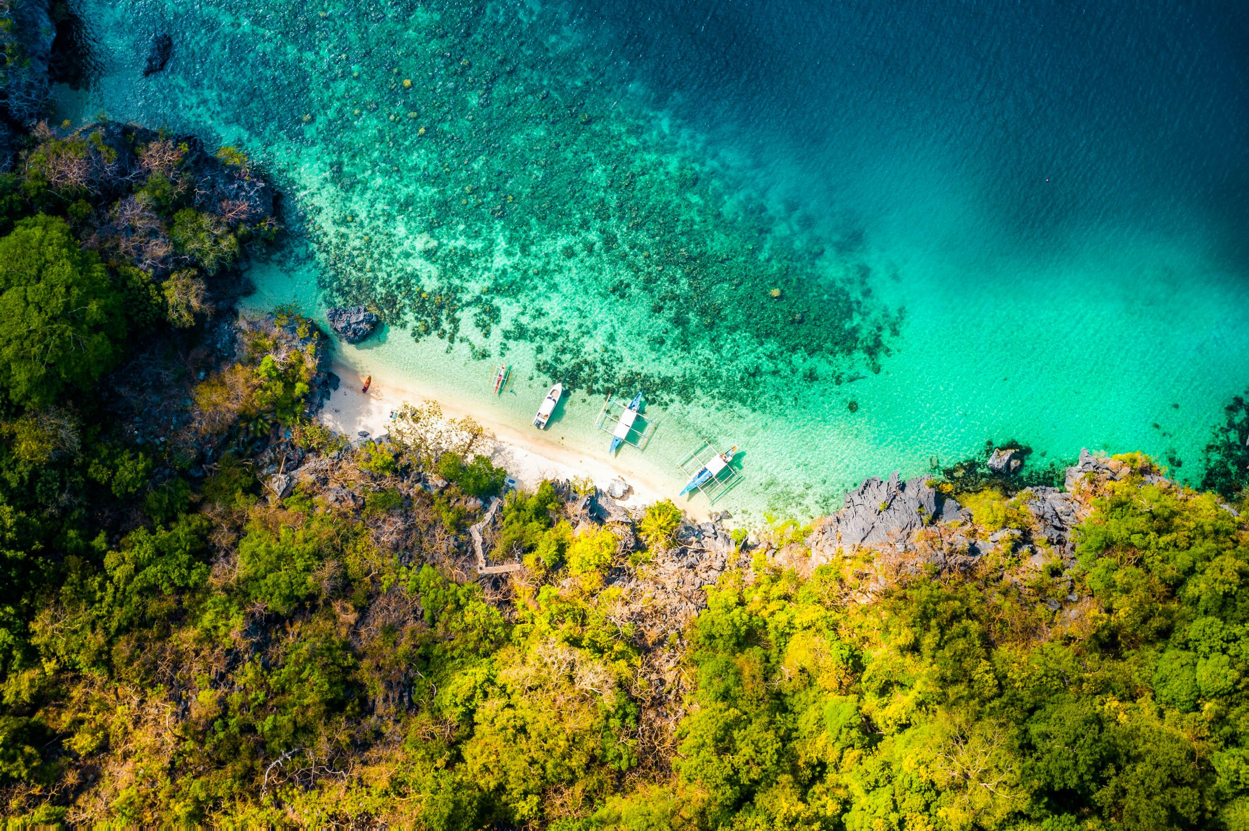 An aerial view of boats docked on a white sand beach bounded between green, rocky cliffs and turquoise waters of El Nido, one of the best places to visit in the Philippines