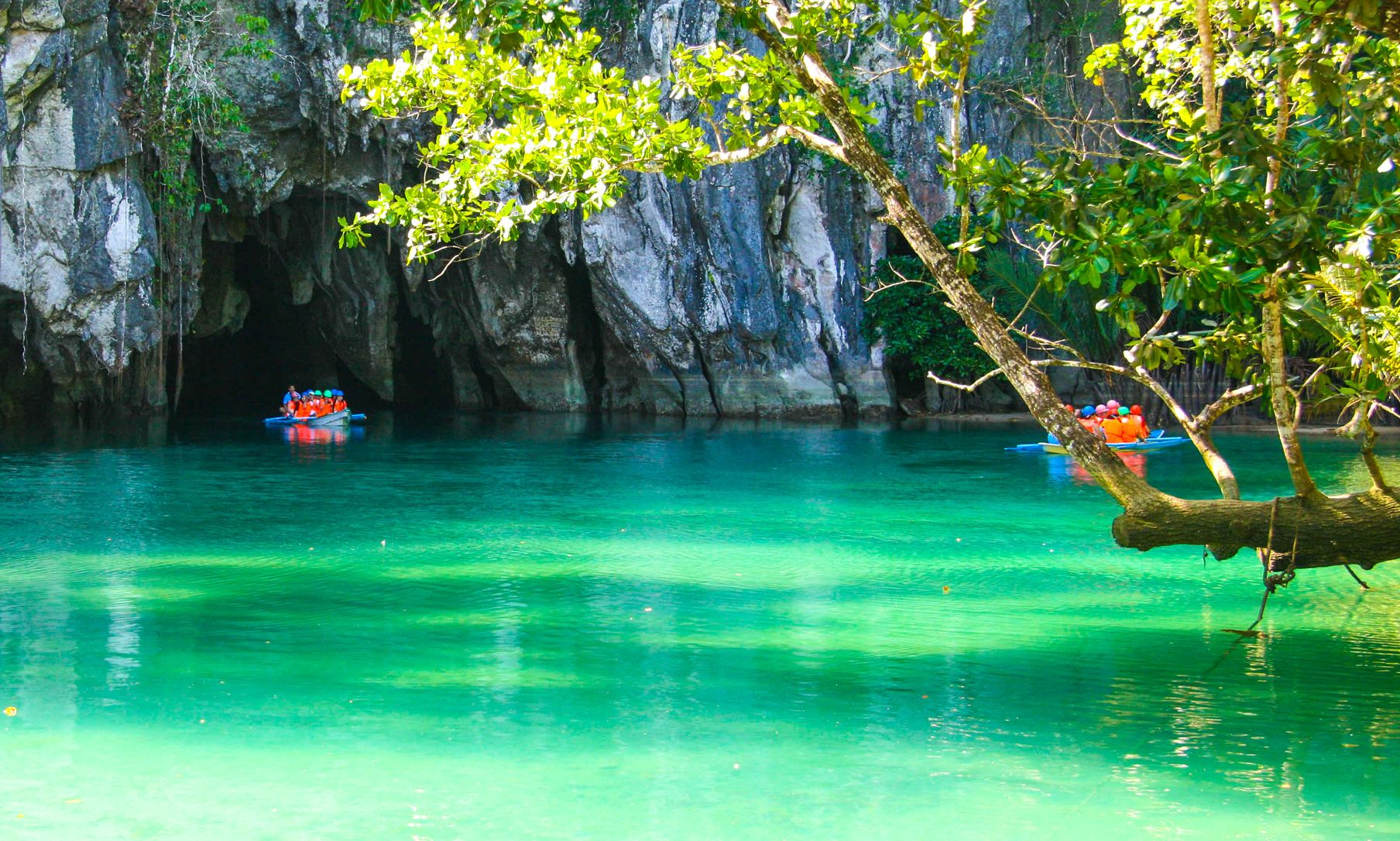 A boat laden with people sails through turquoise- and jade-hued waters and into a cave opening on a limestone cliff overhung with vegetation
