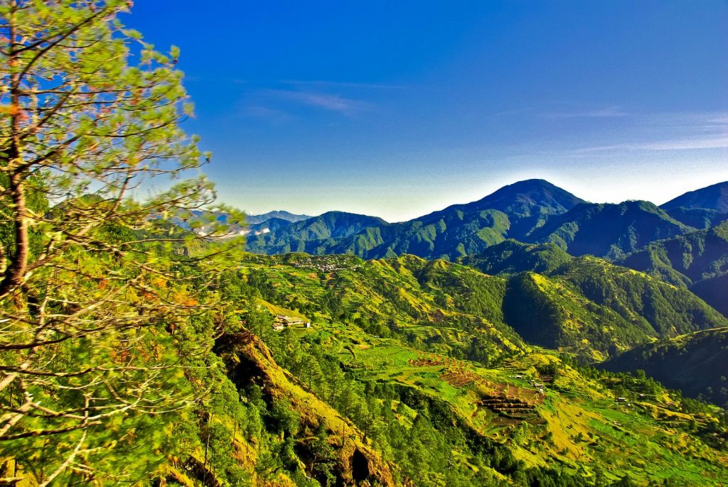 verdant mountainous terrain beneath a blue sky in Sagada, one of the best places to visit in the Philippines