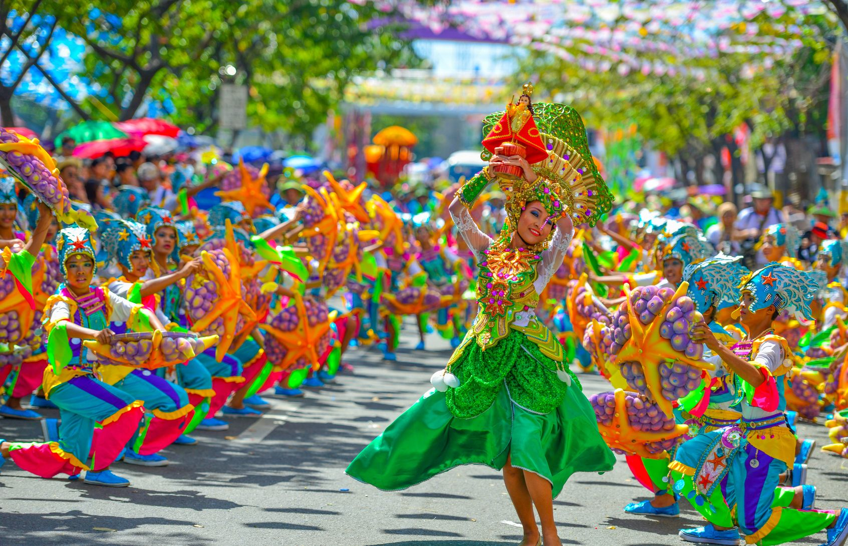 Participants of a local festival clad in colorful costumes dance on the streets in Cebu City, one of the best places to visit in the Philippines
