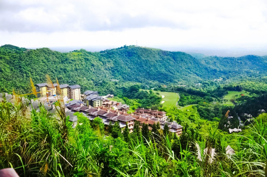Row of buildings and houses nestled on a green pine- and grass-clad mountainside in Tagaytay City, one of the best places to visit in the Philippines