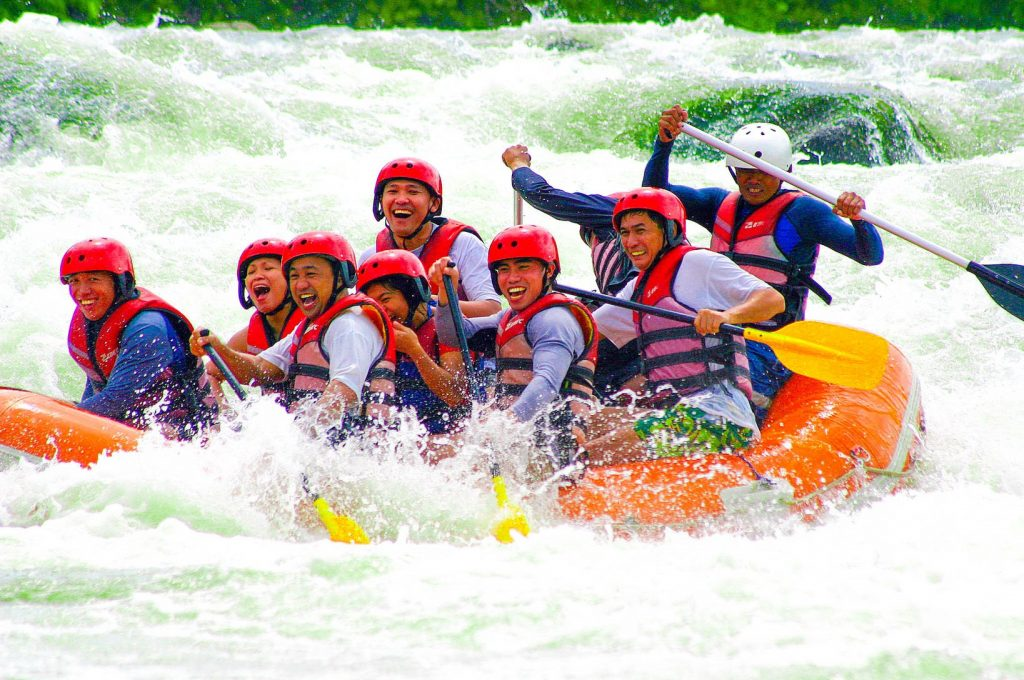 A group of people wearing life vests white water rafting on an orange inflatable boat along a river in Cagayan de Oro, one of the best places to visit in the Philippines
