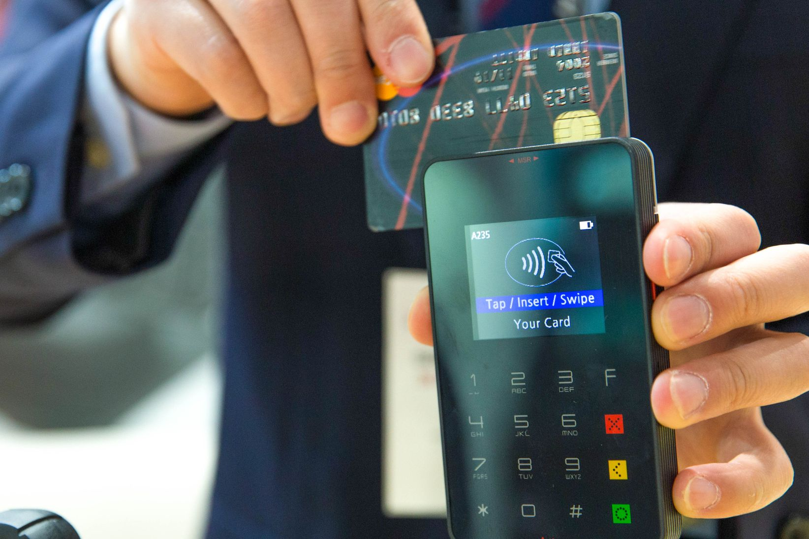 Among the benefits of having an emergency fund is that you reduce the need to rely on credit card debt, as indicated by a credit card being swiped on a credit card terminal