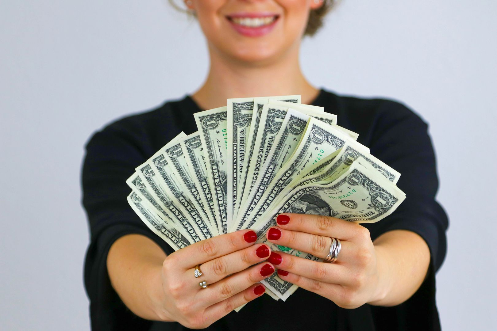 Woman holding out an unfurled wad of dollar bills, indicating that among the benefits of an emergency fund is that it allows you to make more money