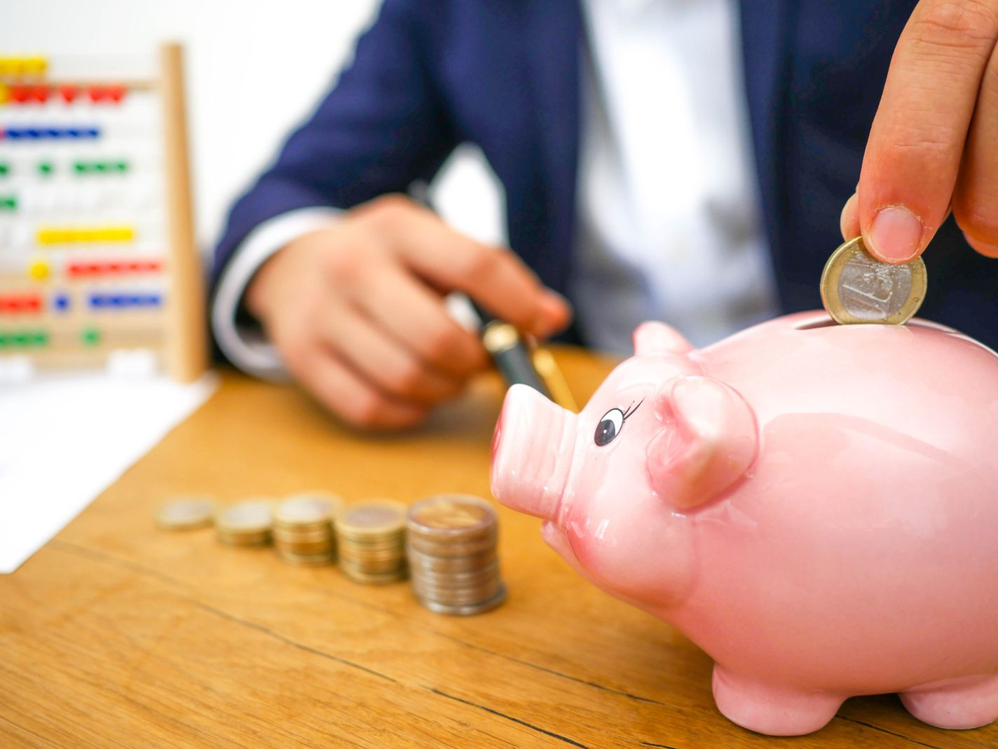 Coins being inserted in a pink piggy bank, indicating that among the benefits of having an emergency fund is that it helps develop good financial habits