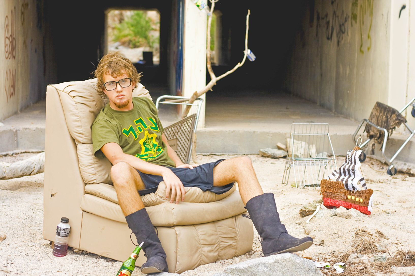 Broke, homeless, and unemployed man sitting on a couch surrounded by dirt and garbage