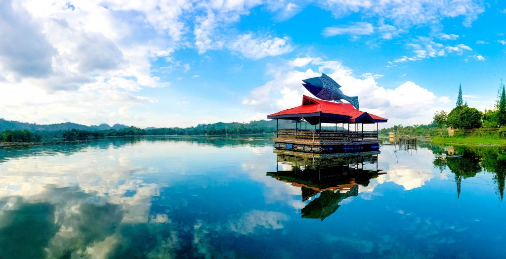A red-roofed building surmounted by a statue of a fish stands upon the clear waters of Lake Sebu, one of the most scenic lakes in the Philippines