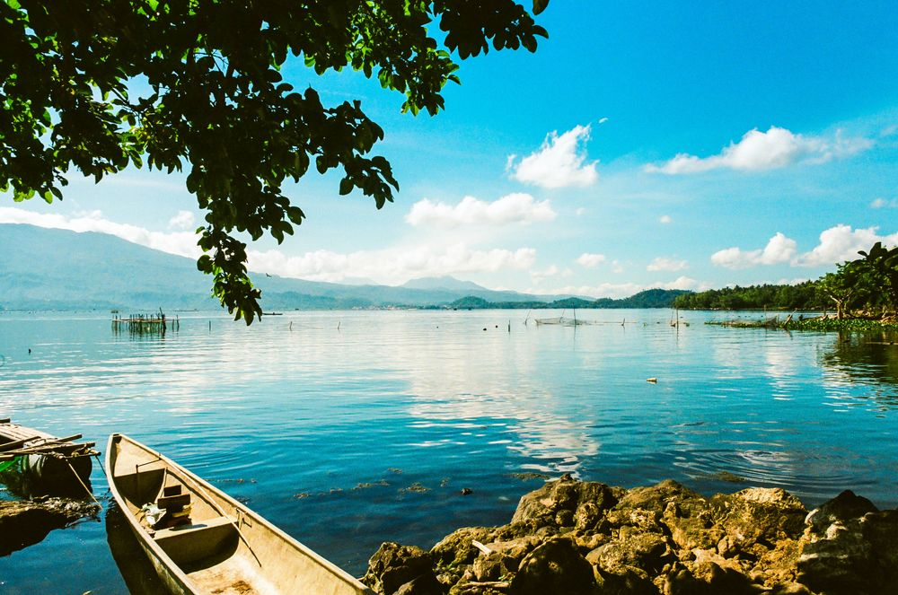 A boat lies moored close to the rocky shoreline of a wide body of water beneath a blue sky in Lake Buhi, one of the most scenic lakes in the Philippines
