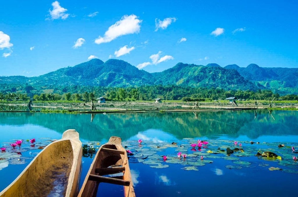Canoes floating along the surface of a clear lake, which reflects the mountains in the distance