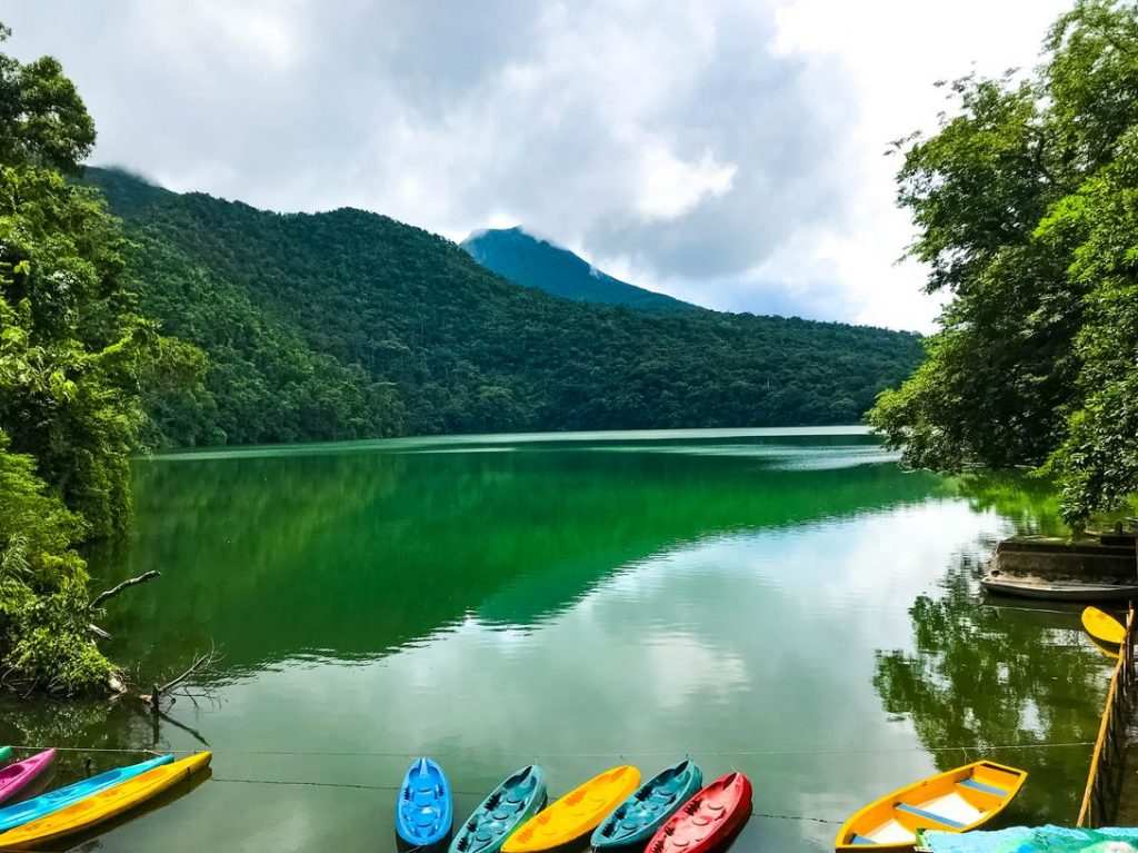 Colorful kayaks on a green lake surrounded by green mountains