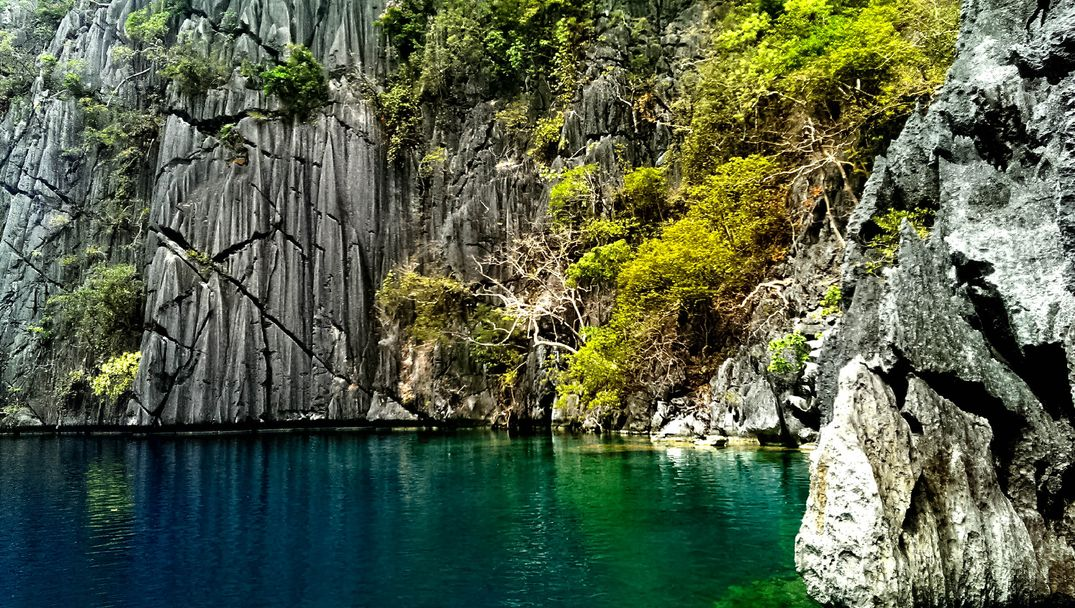 Limestone cliffs overhung with vegetation rise above the green and blue waters of Barracuda Lake, one of the most scenic lakes in the Philippines