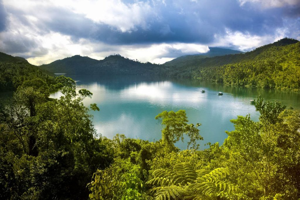 Inland body of turquoise water surrounded by forests and mountains
