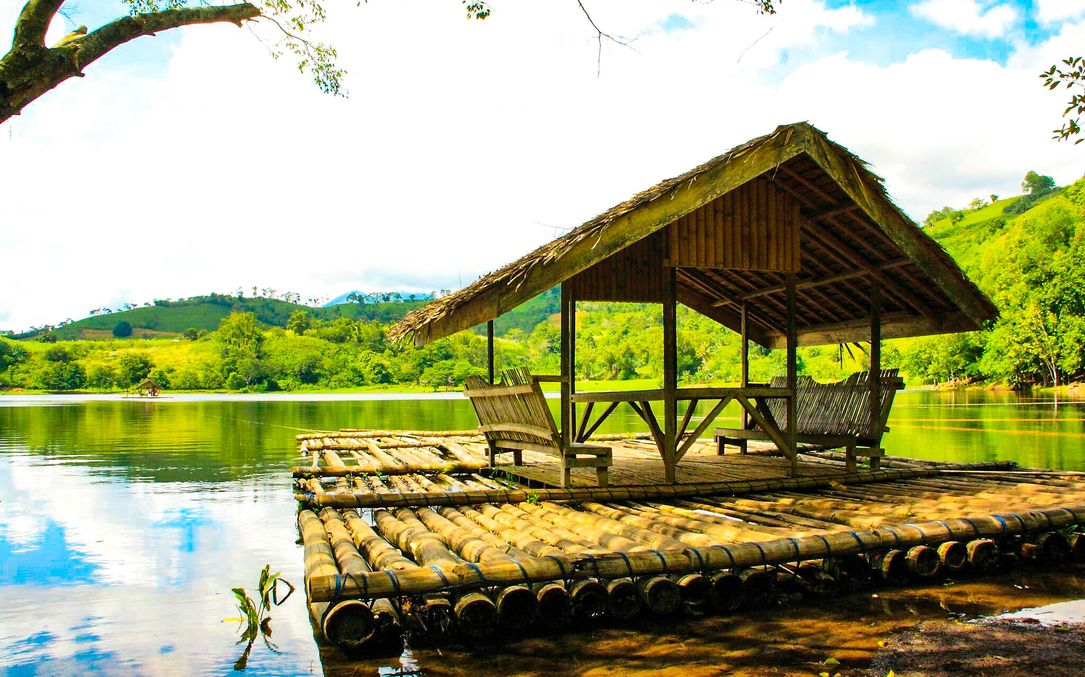 Thatched hut built atop a bamboo raft, floating on the edge of Lake Apo, one of the most scenic lakes in the Philippines