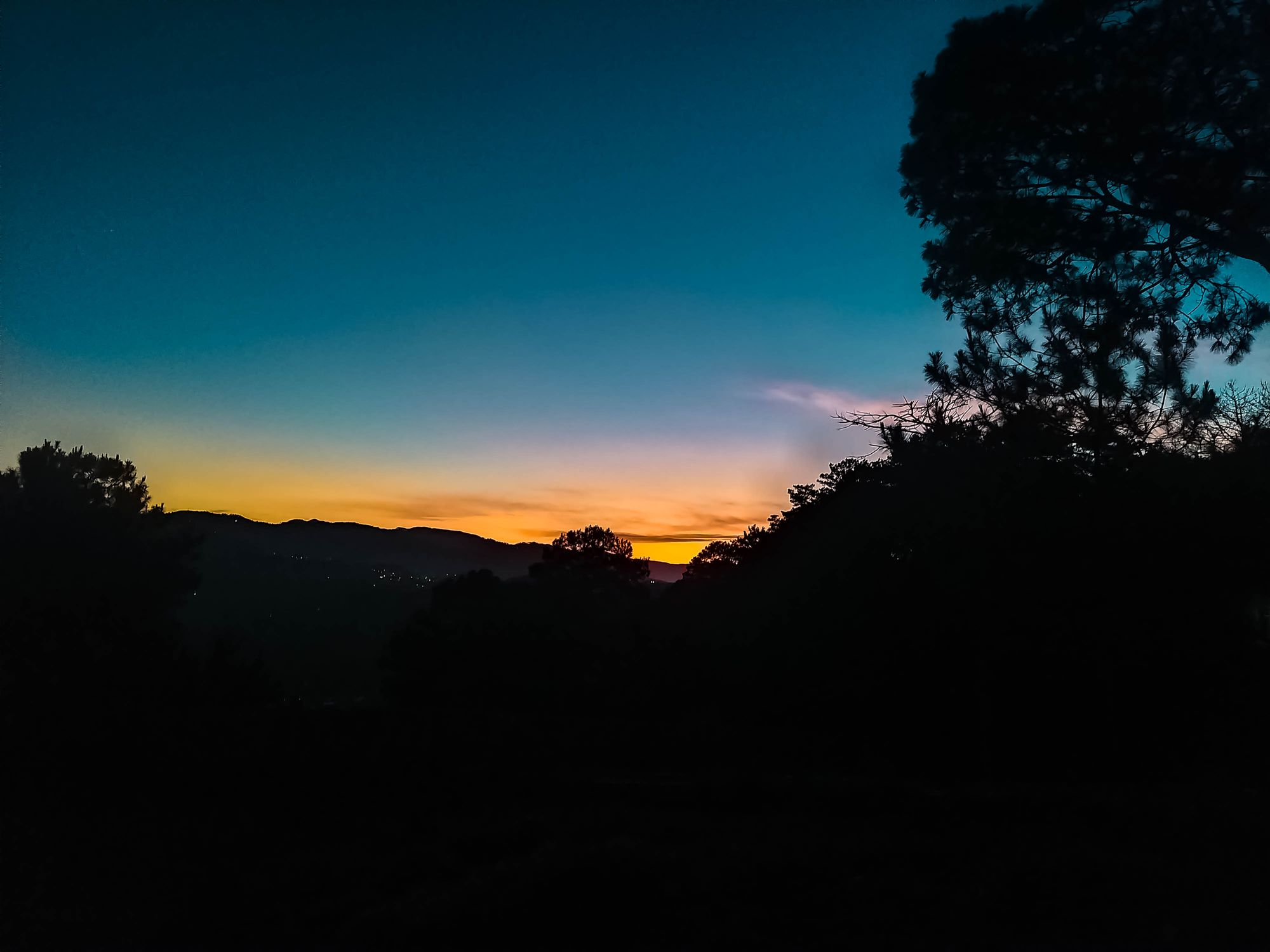 A picture of the dawn sky in blue, orange, yellow, and pink hues at Mount Kalugong