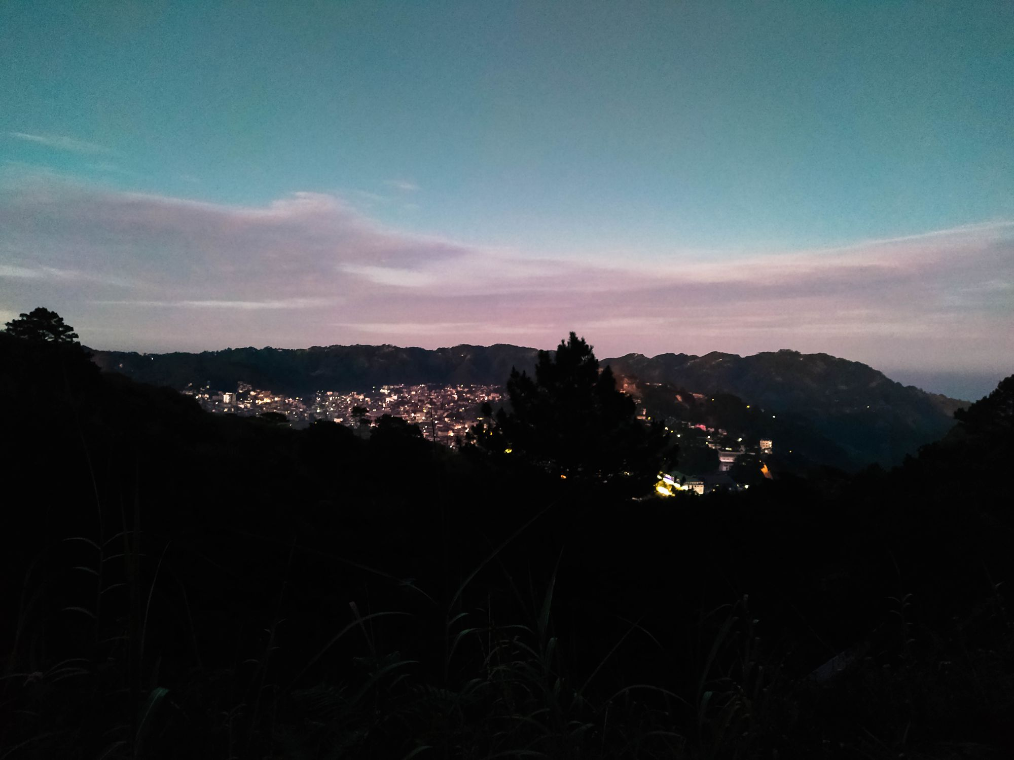 Valley town with many twinkling lights beneath a dawn sky at Mount Kalugong