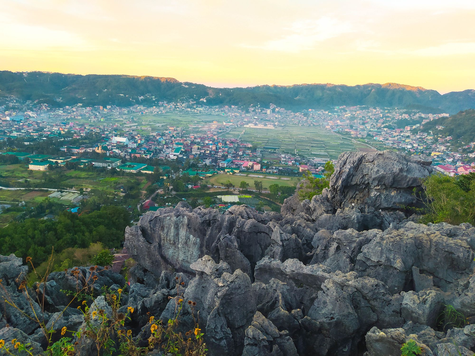 Limestone rocks overlooking a misty valley town surrounded by hills and mountains beneath an early morning sky