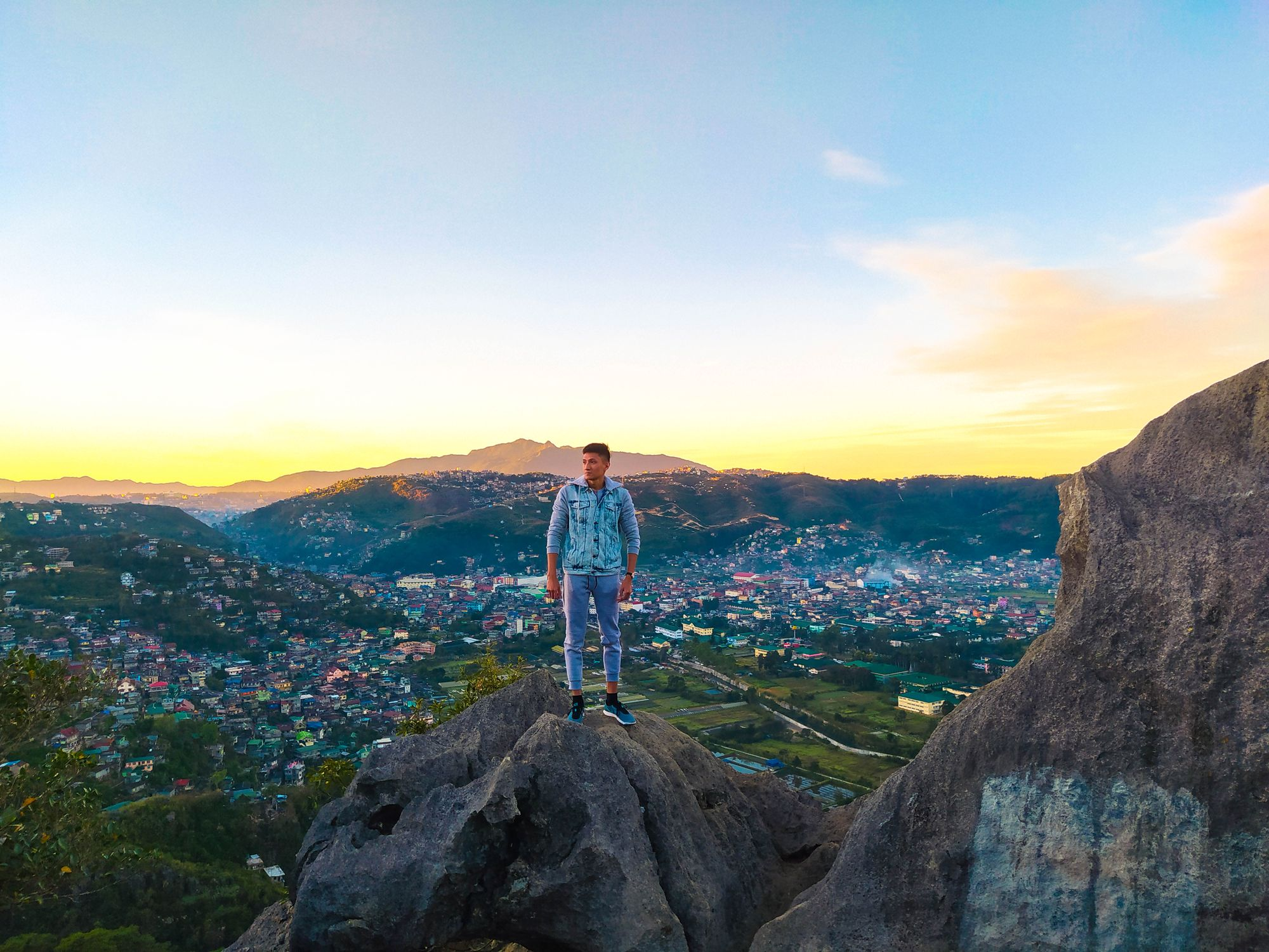 A man standing on a rock overlooking a valley town surrounded by hills and mountains beneath a morning sky