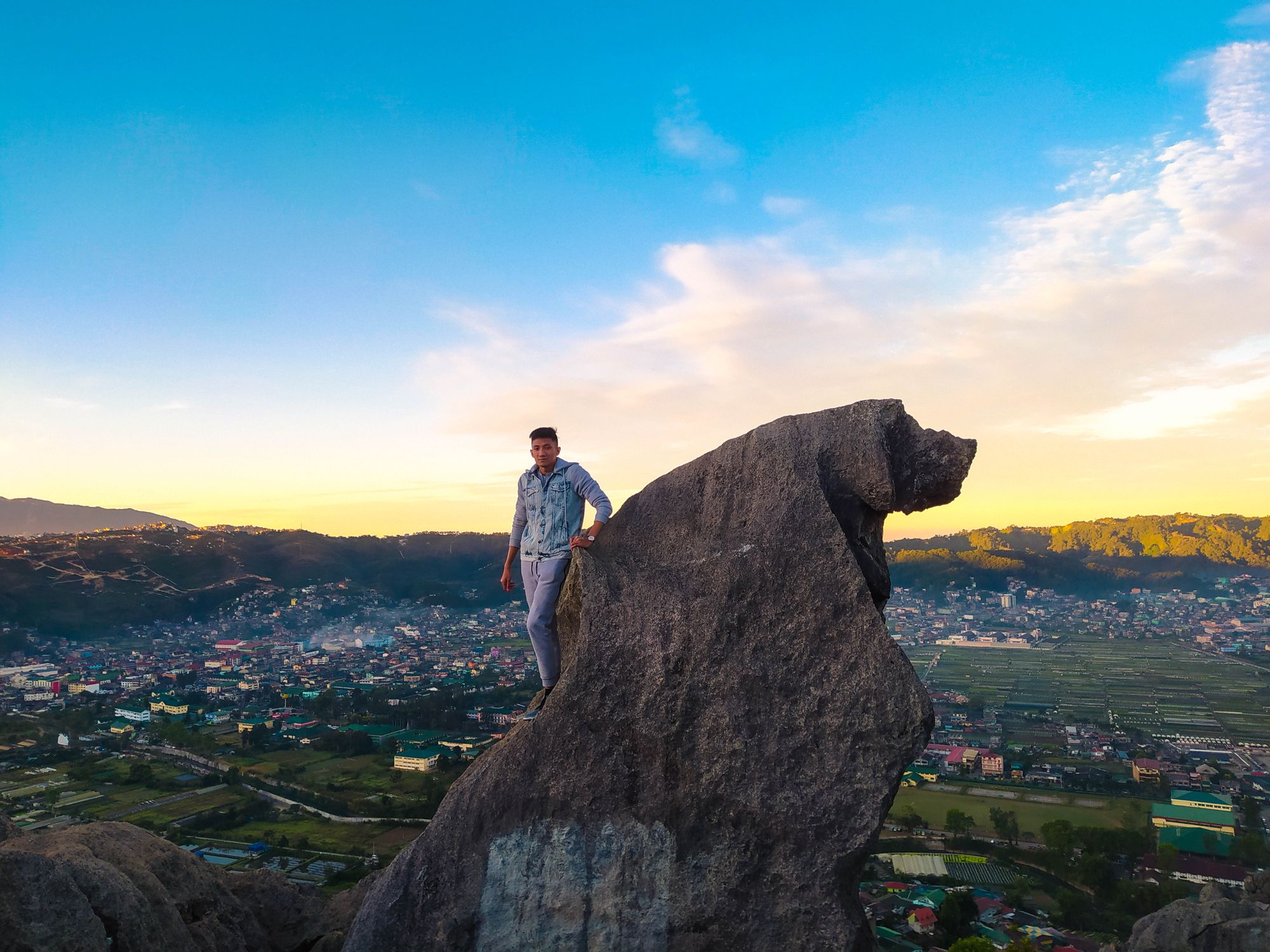 Man standing on a large rock overlooking a valley town surrounded by hills and mountains beneath a morning sky