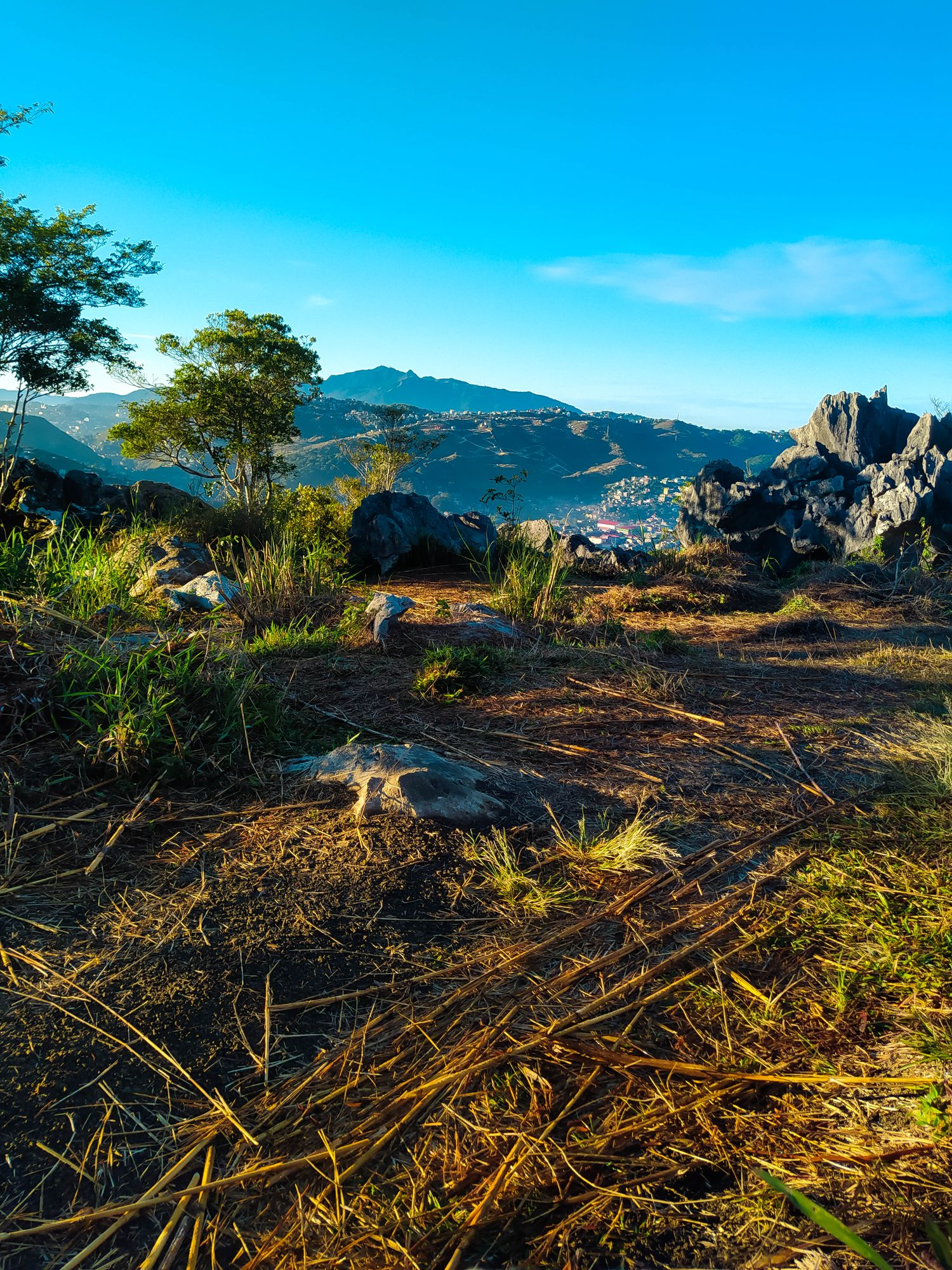 Grass-clad terrain riddled with limestone rocks and a few trees overlooking a valley town surrounded by mountains in the distance at Mount Kalugong