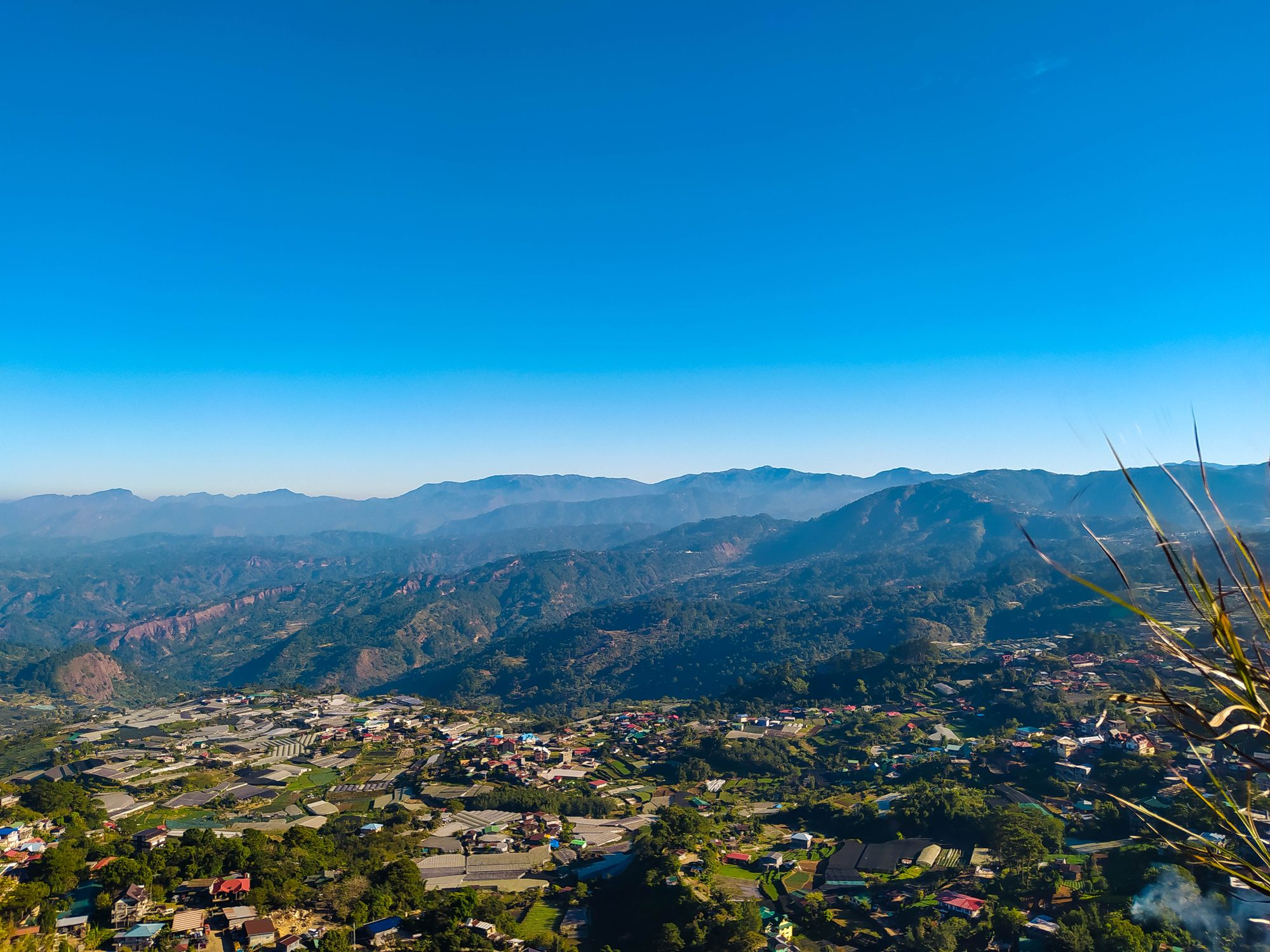 A valley town surrounded by a mountain range beneath a clear blue sky