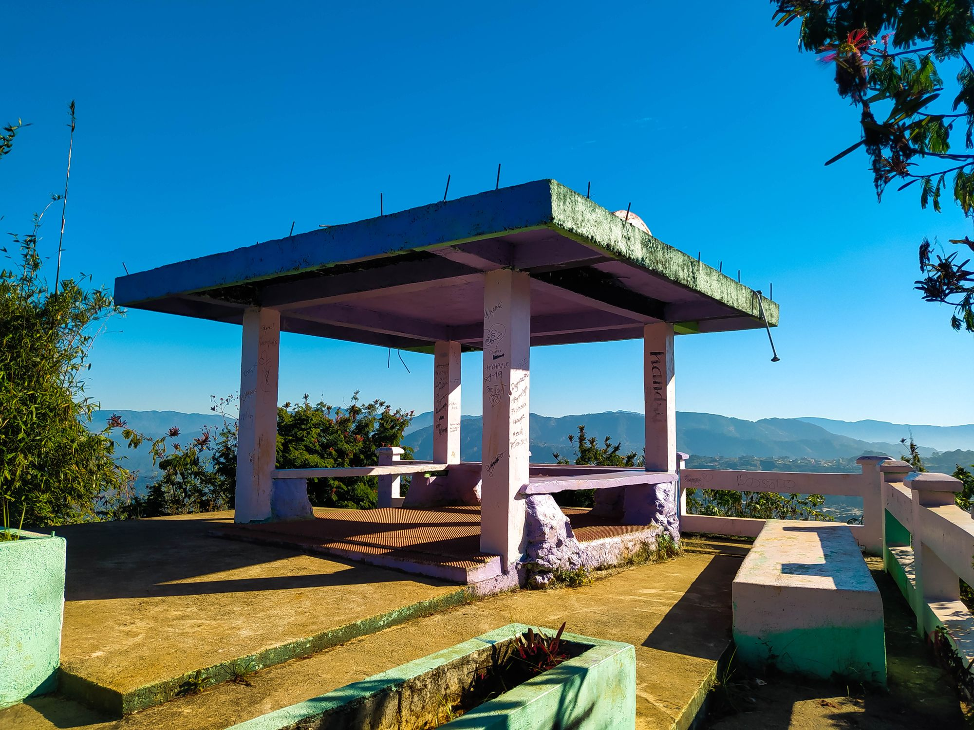 A concrete view deck overlooking a view of mountains