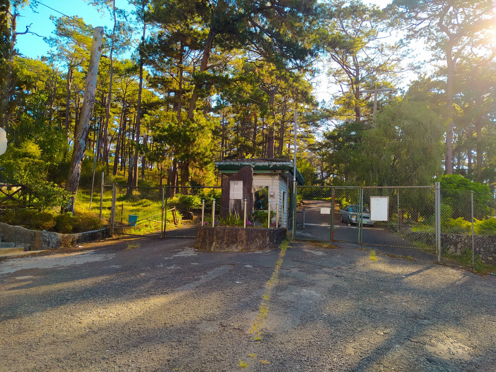 Chain link gates and a guardhouse barring a concrete road near the Camp John Hay's Eco-Trail