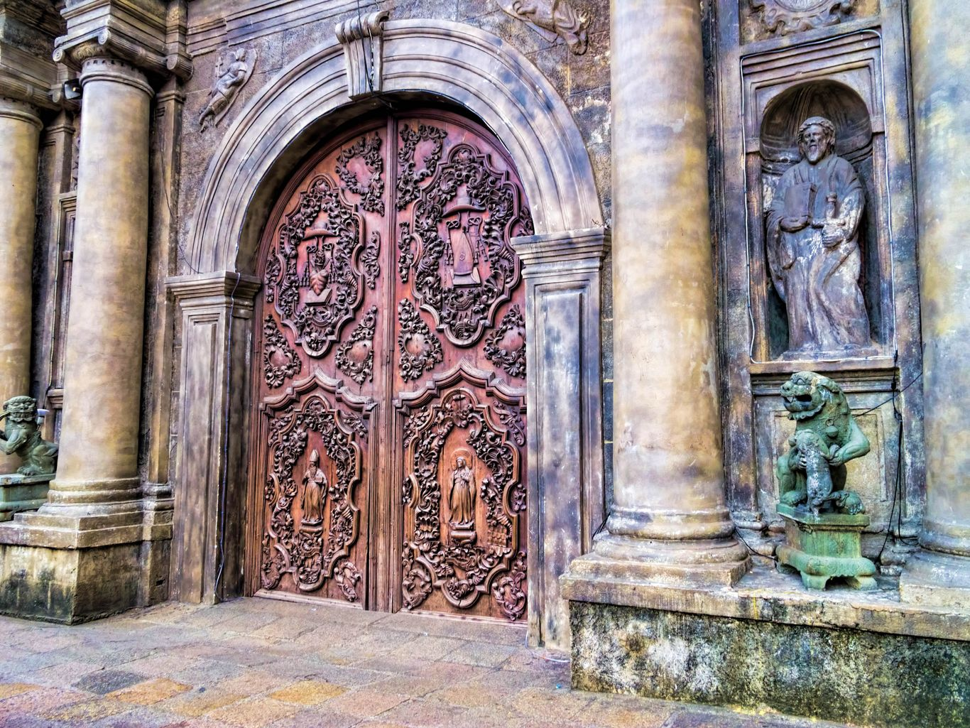 The intricately carved doors of an old stone church flanked by stone pillars, statues, and engravings